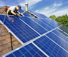 Solar technicians install solar panels on the roof of a home.