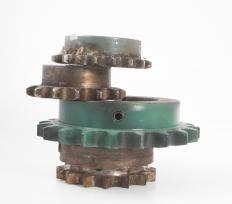 A chain drive rotates around sprockets that have tooth-lined edges.