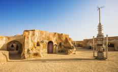Suspension of disbelief occurs when an audience that is watching the original Star Wars movie accepts that people who have robots and spaceships would live in huts made out of mud and sand in the desert.