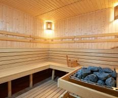 A steam bath room with wooden benches and sauna stones.