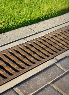A stamped concrete driveway often causes rain water to run into a storm drain system.