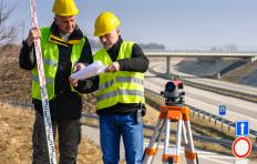 A quantity surveyor trainee assists the main quantity surveyor at a construction job site or office position.