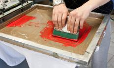 Ink is pressed through a stencil in the silk screen printing process.