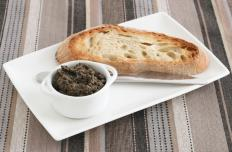 Tapenade in a ramekin, served with a slice of bread.