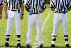 Multiple officials oversee a football game.