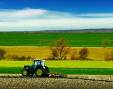 A farmer uses a tractor to till a field.