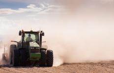 Farming operations use large tractors to pull seed planters across fields.