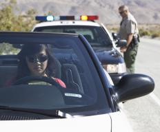 Woman sitting in her car after being pulled over by the police.