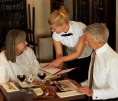 A waitress explains the menu to her customers, subtly up-selling certain items.