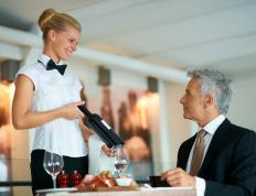 A sommelier showing a bottle of wine to a customer.