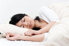 A woman asleep on a cervical pillow.