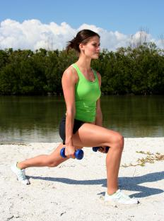 A woman doing a dumbbell lunge.