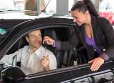 A sales representative in a car dealership works to generate revenue by selling cars to interested buyers.