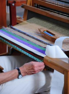 The heddle of a loom controls the warp threads, which run vertically down the device.