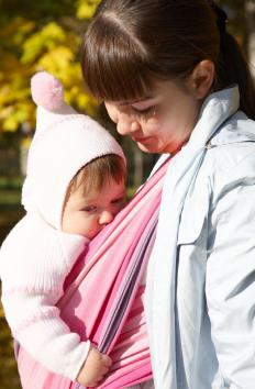 A baby sling makes it possible to care for an infant while having hands free to help an older child.