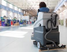Commercial floor scrubbers are available as walk-behind versions or riding types.