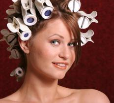 Putting hair in rollers is the first step to a French twist for someone with straight hair.