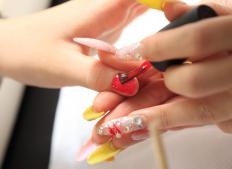 Salon technicians apply the mixture of acrylic powder and monomer liquid with a soft bristle brush to the client's nail.