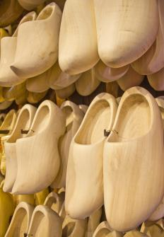 Clogs are backless, closed toed wooden shoes that feature heels no more than a couple of inches high.