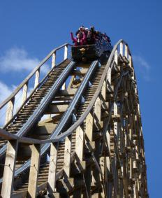 Kinetic energy is released as roller coaster riders descend over a hill.