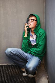 A prototypical hipster wears a hooded sweatshirt and wears thick-rimmed glasses.