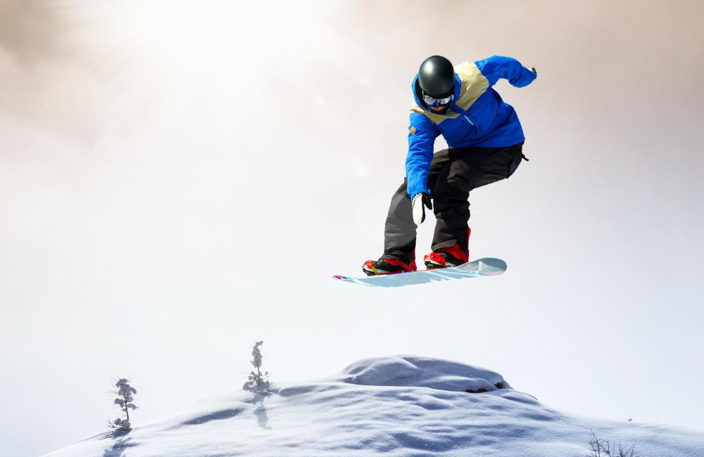 A snowboarder performs an ollie by transferring his weight from the front to the back of the board.