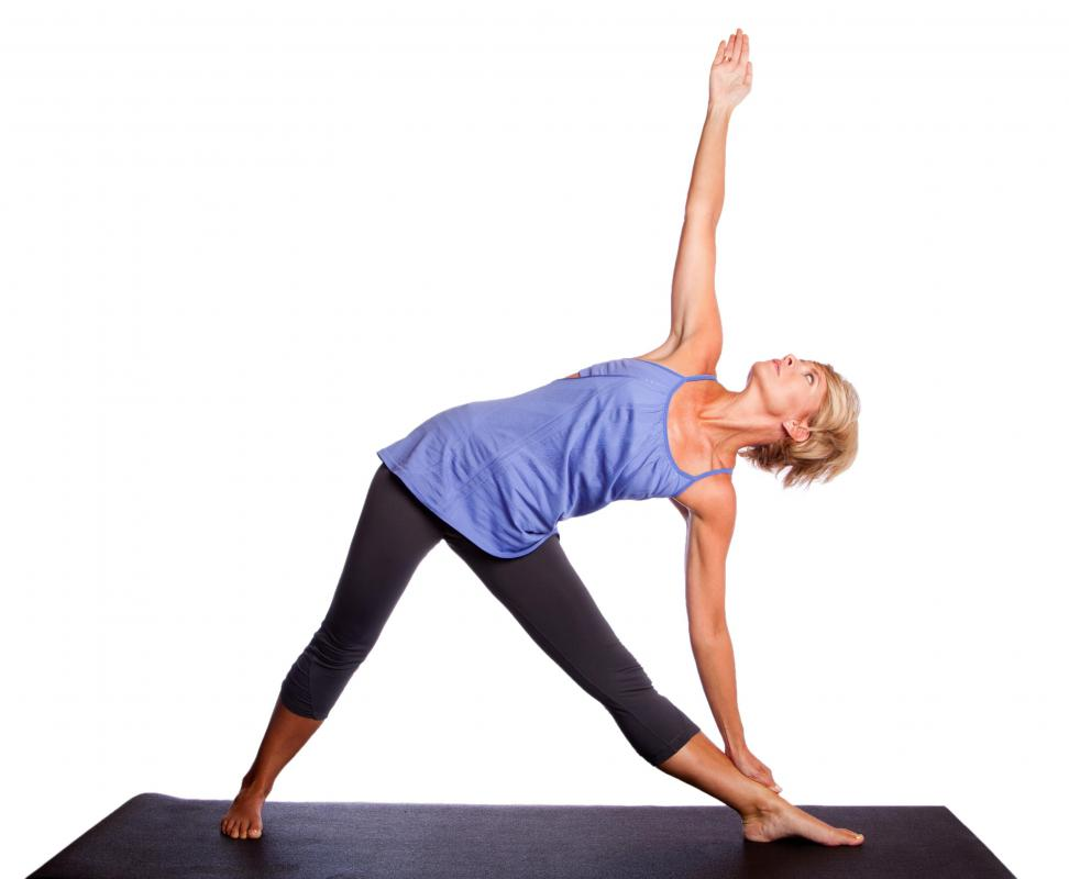 A woman performing Triangle Pose on a yoga mat.