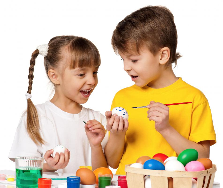 A girl and boy painting Easter eggs.