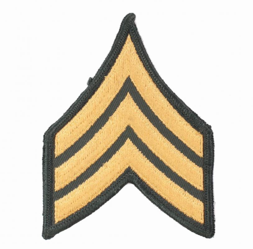 The US Army rank of sergeant, an NCO, is indicated by a uniform patch with three chevrons.