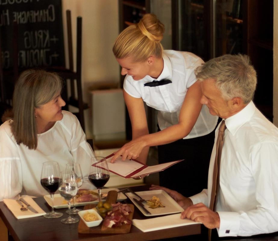 A waitress explains the menu to her customers.