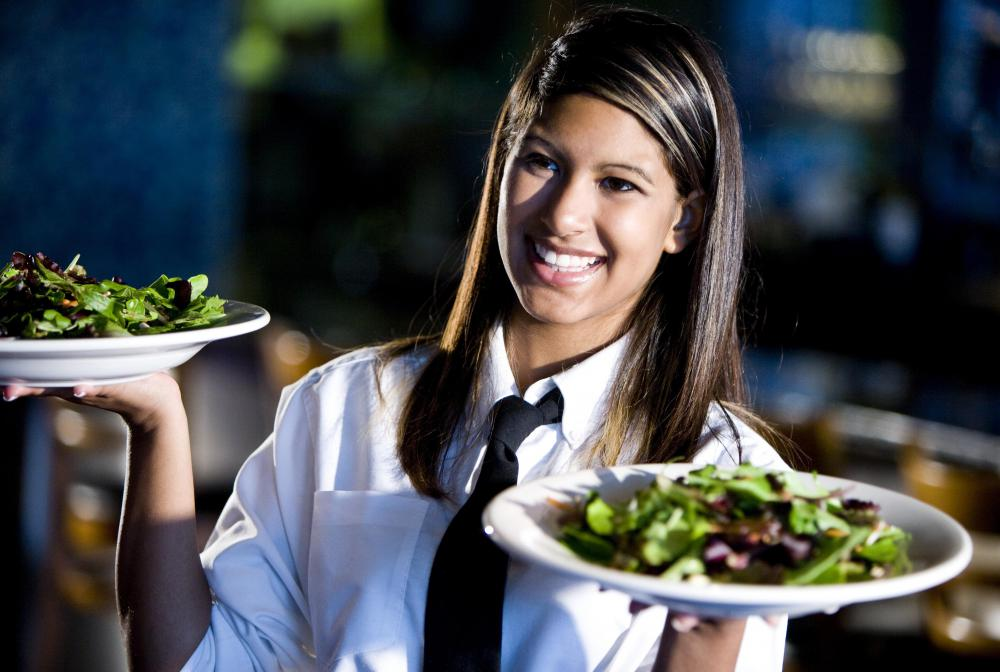 A waitress delivers food to customers at a restaurant.