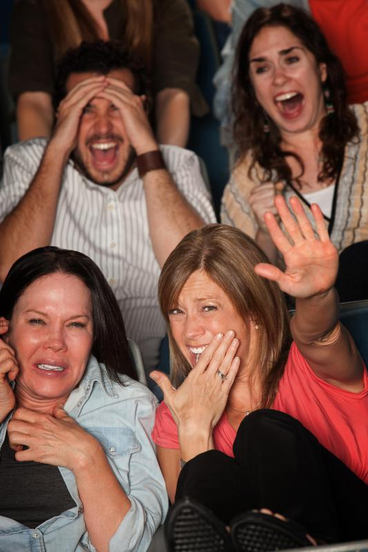 People watching a scary movie in a movie theater.