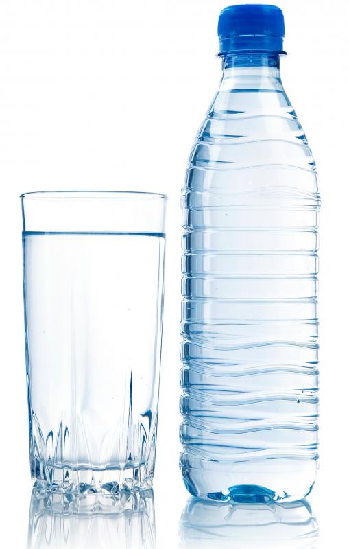 A glass of filtered water beside a bottle of water.