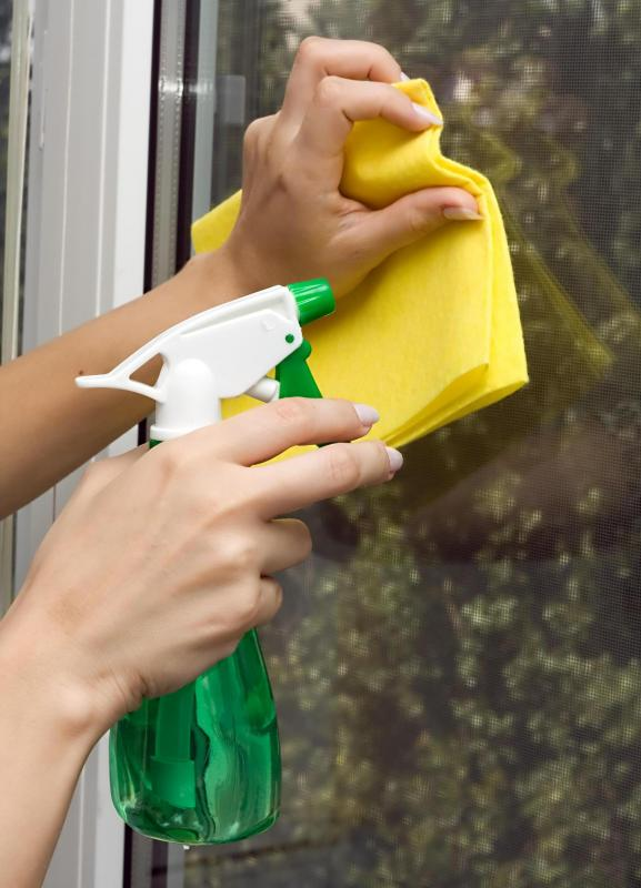 A woman cleaning a window with a chamois.