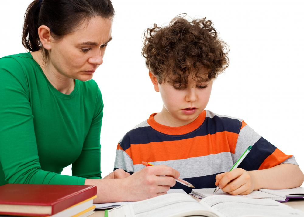 A woman helping a boy with dyslexia.