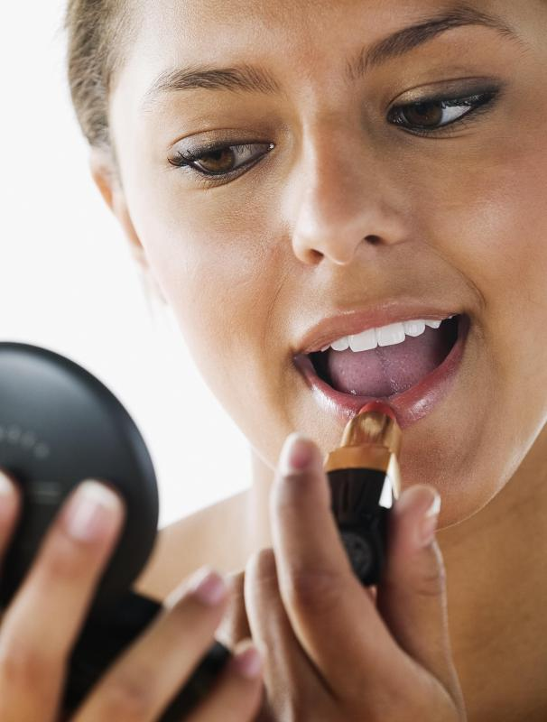 A woman applying lipstick, one type of cosmetic.