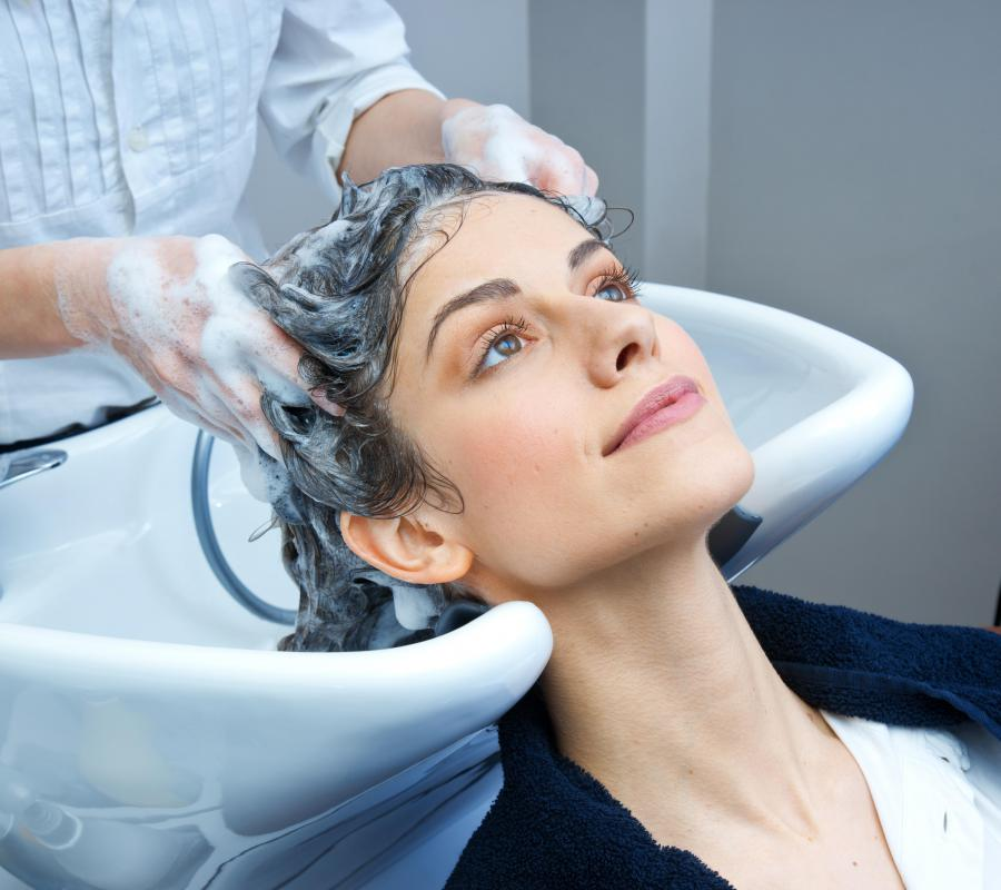 A shampoo cape is worn in a salon to prevent an individual from getting wet.