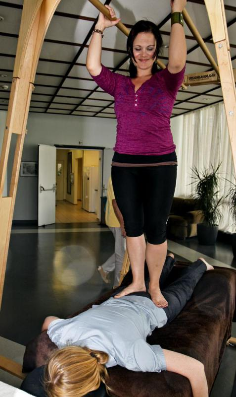 A therapist walks on a client's back and utilizes bars to vary pressure and weight during ashiatsu.