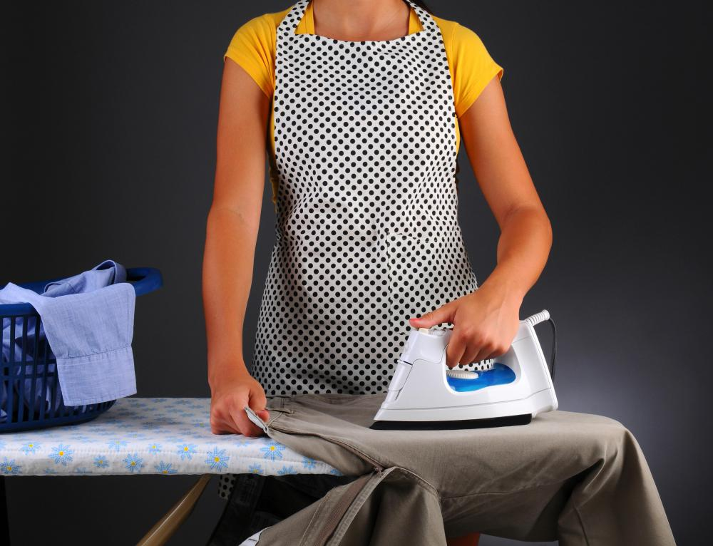 A lady's maid tends to her employer's clothes, making sure they are clean and pressed.