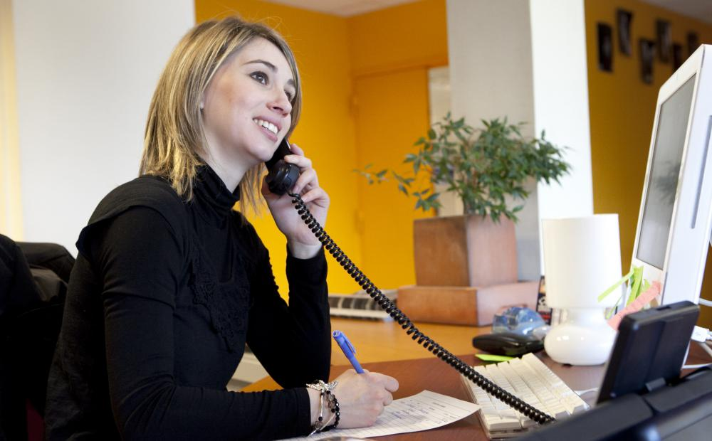 An administrative assistant typically fields phone calls and greets clients.