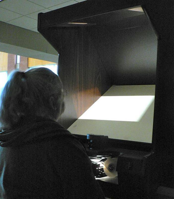 Woman using a microfilm reader.