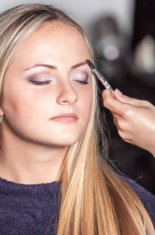 An eyebrow brush may be used to apply a darkening powder to the eyebrow.