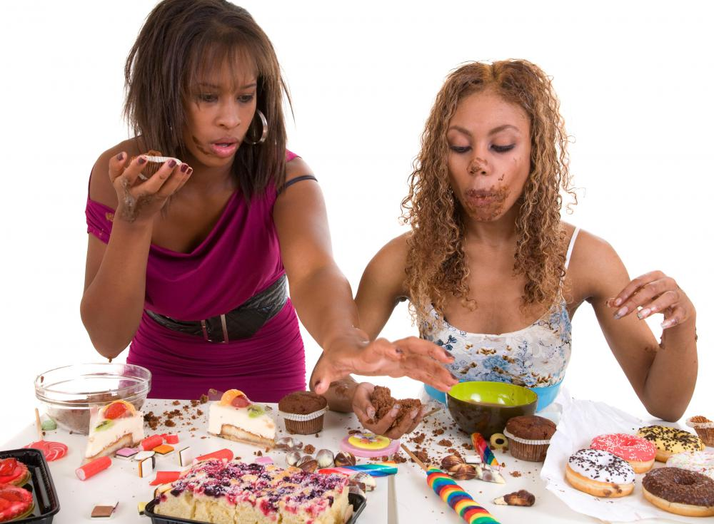 https://images.wisegeek.com/women-eating-junk-food-against-white-background.jpg