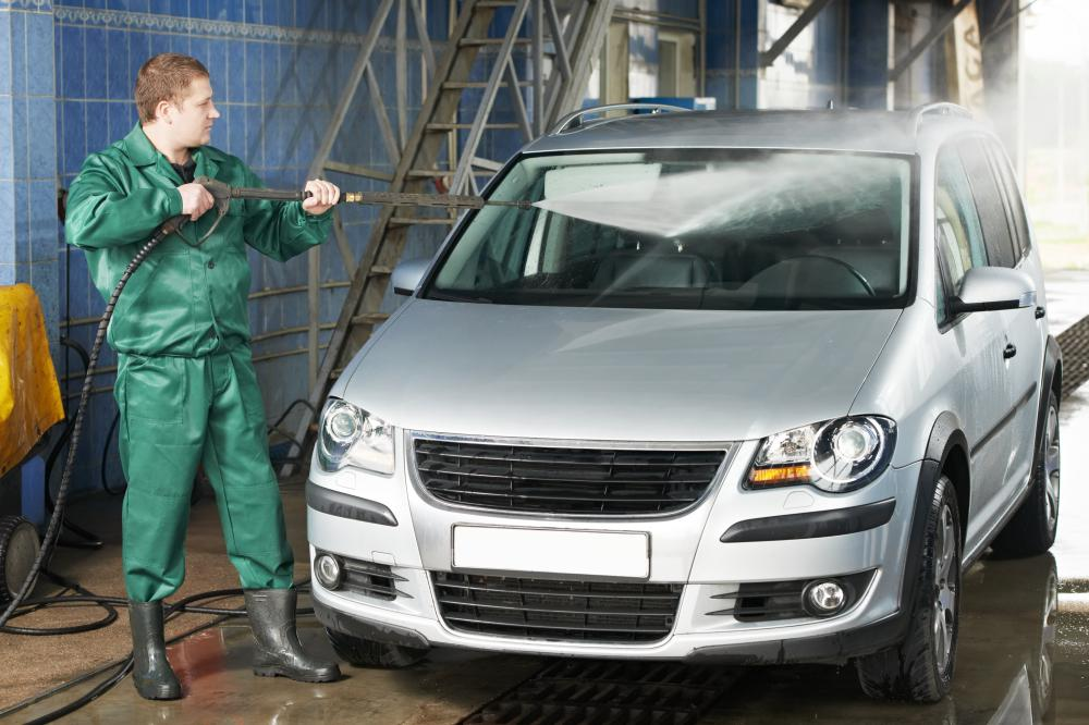cars are washed with high pressure sprayers during a brushless car wash