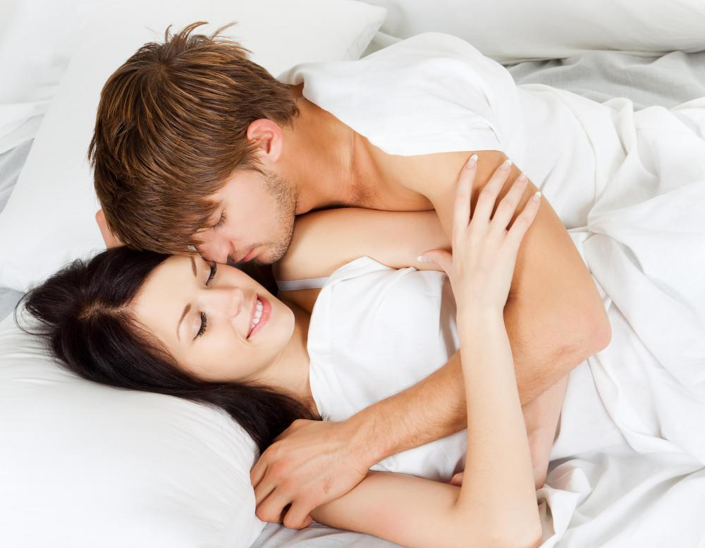 man and woman kissing and touching in bed